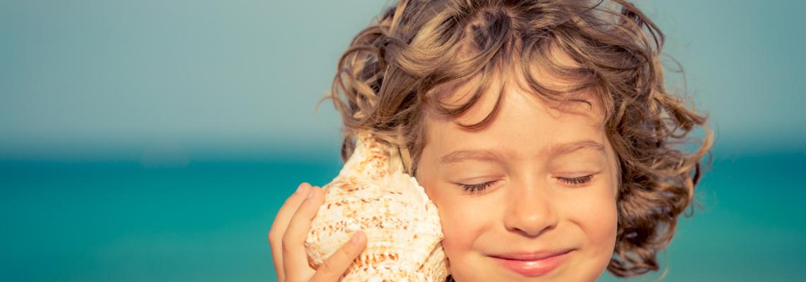 Kind mit Muschel am Ohr